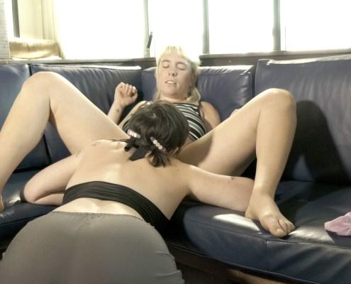 Kneeling on the floor, Lola performs oral sex on Olivia.