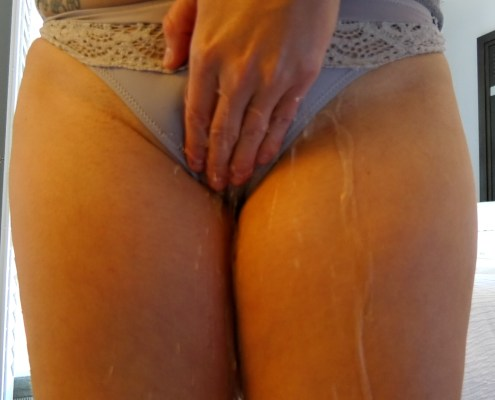 While holding herself, Alisha pees in her panties, with visible streams escaping between her fingers.