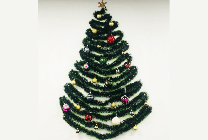 Árbol de navidad artificial de año nuevo de la oropel en la pared con sus propias manos.