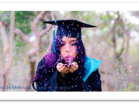 College graduate in gown blowing confetti.