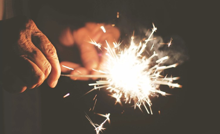 Photo by Kelley Bozarth on Unsplash shows an older hand lighting the sparkler held by another in a metaphor for transferable-skills and education that serves a bigger purpose.