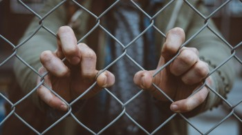 Man trapped behind chain link fence. Many barriers prevent or interfere with success in college.