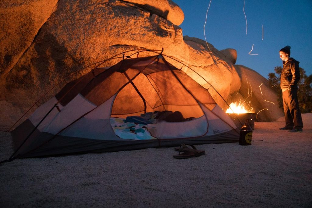 Camp fire next to tent in Joshua Tree