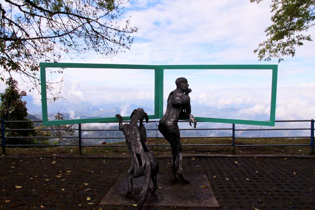 Manizales Sculpture of man and dog looking out of a window