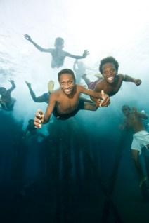 No Model Release. Boys jumping and swimming under Jonny's Jetty, Kokopo/Rabaul, Papua New Guinea