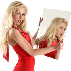 Beautiful girl in red clothes looks in a mirror