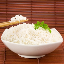 Closeup of rice on chopsticks and a bowl on mat