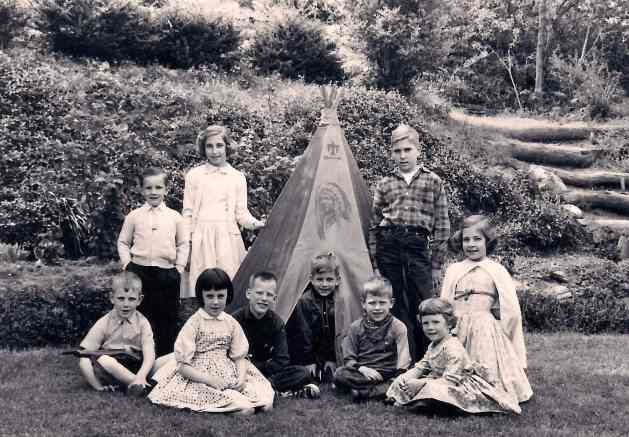 245 Crest Drive, my brother Steve peeking out of the teepee, the writer is in a plaid shirt, my sister Liz left of teepee, my sister Lorraine kneeling at right
