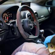 Person wearing gloves in driver seat of car