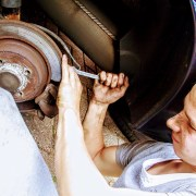 auto mechanic using wrench on wheel
