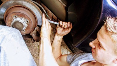auto mechanic using wrench on wheel