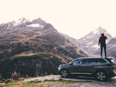 person standing on SUV in front of mountain