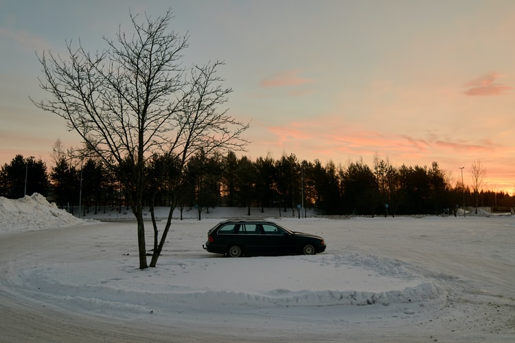 car in snowy parking lot during sunset
