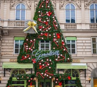 christmas tree decoration on building with cars parked in front