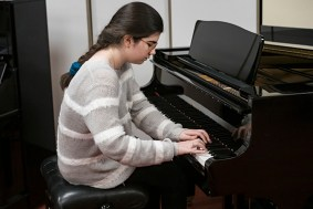 girl pupil plays music on the piano