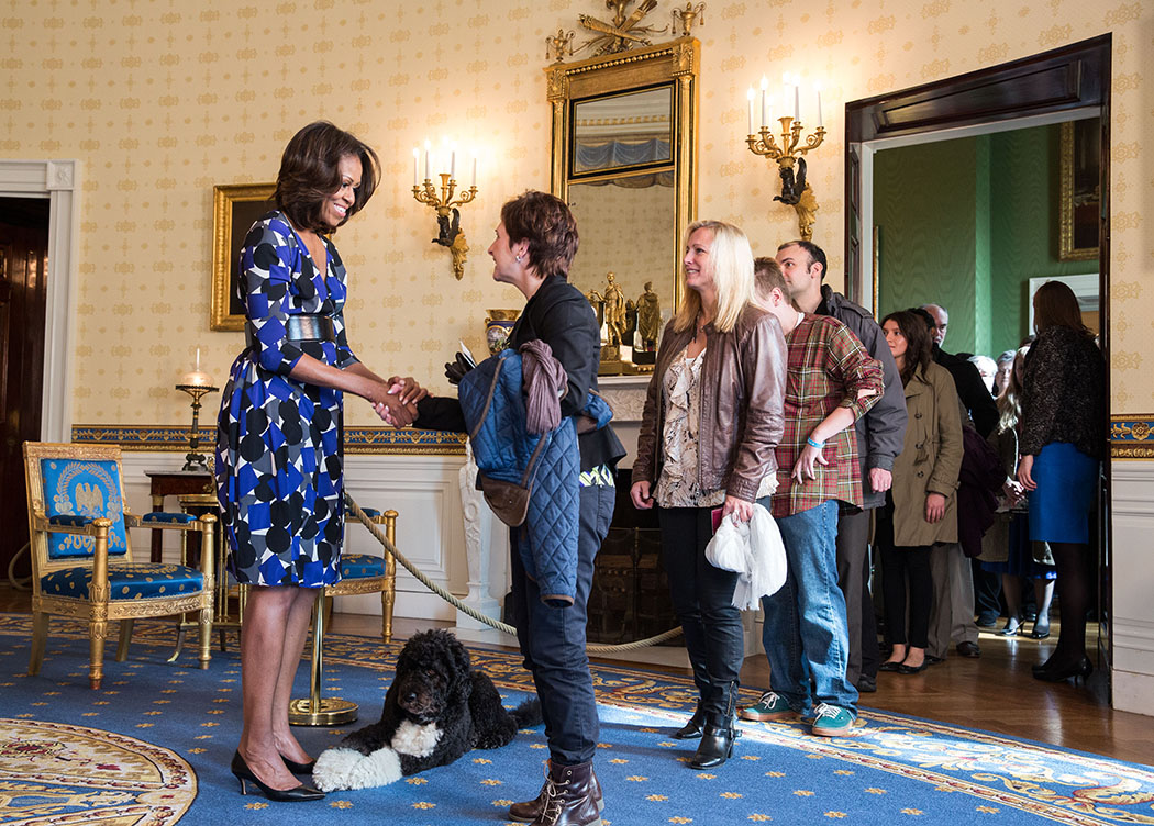 First Lady Michelle Obama, with Obama family pet Bo, greets visitors in the Blue Room during a White House tour, Nov. 5, 2015. (Official White House Photo by Amanda Lucidon)