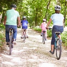 Family riding bikes on trail
