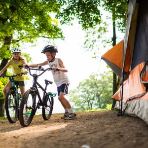 Kids pedal bicycles near a tent at Wyalusing State Park, Wisconsin