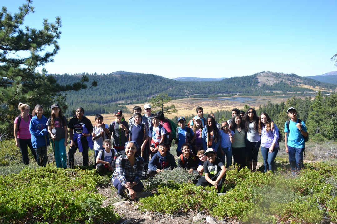 Students taking a break from hiking at an overlook on their science field trip.