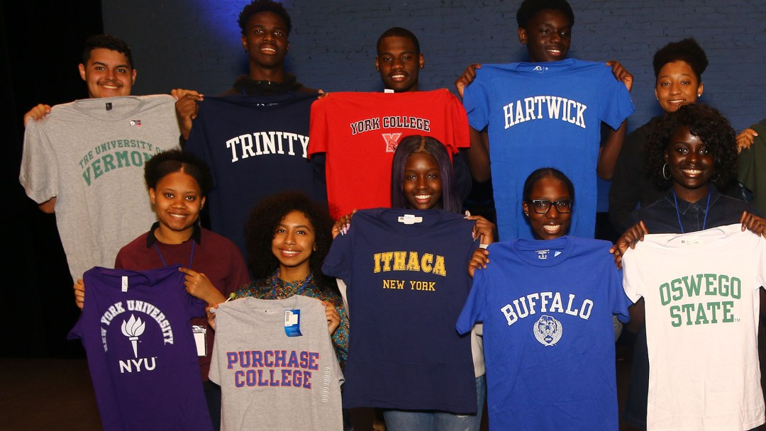 A group of HEAF students hold up their college shirts