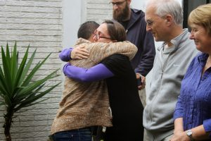 Man hugging woman to comfort her with relatives looking on