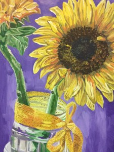 two sunflowers in glass jar with purple background and gold ribbon