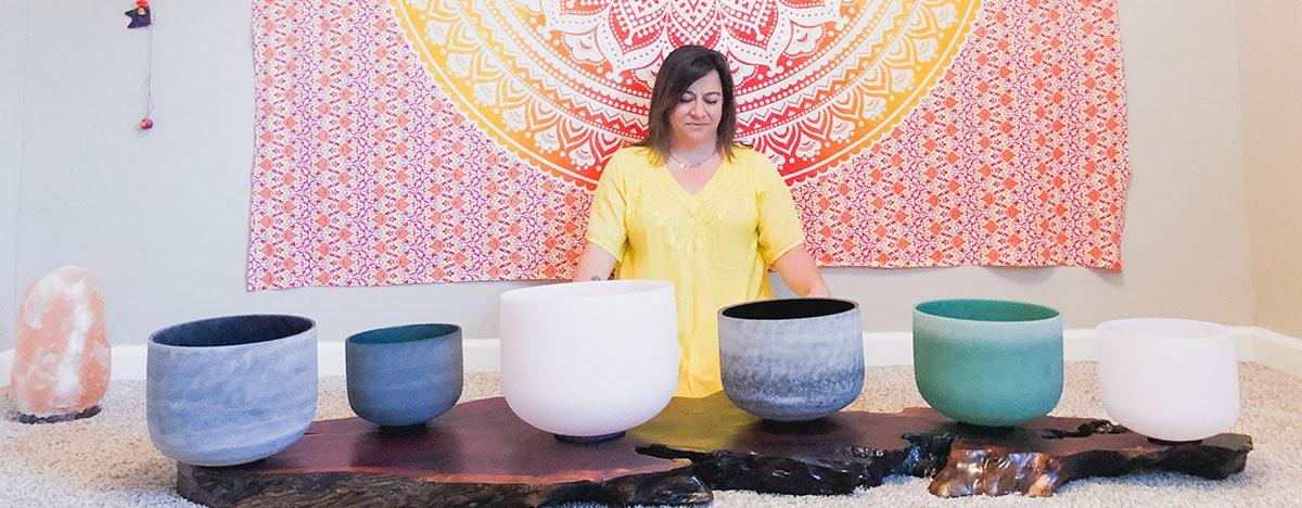 practitioner sits behind sound bowls