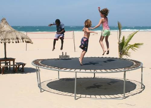 Kids Bouncing on Trampoline at Beach