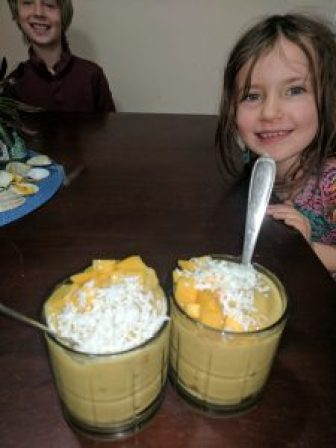 Mango smoothie with shredded coconut and fresh mango pieces make us smile!