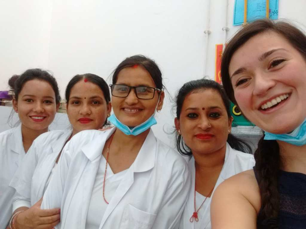 Five people smile, the four on the left wearing white coats.