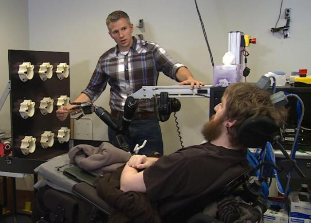 Researcher Rob Gaunt prepares Nathan Copeland for brain computer interface sensory test. This material relates to a paper that appeared in the 12 October 2016, issue of Science Translational Medicine, published by AAAS. The paper, by S.N. Flesher at University of Pittsburgh in Pittsburgh, PA, and colleagues was titled,
