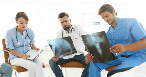 A female physician looking at an x-ray with two other male doctors