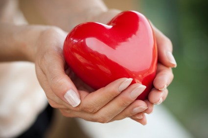 Holding a heart in cupped hands. Love and health care concept.