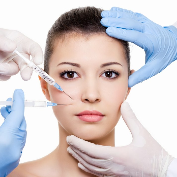 Plastic surgeons giving injection of botox in female lips - isolated white