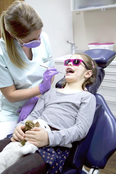 Kinderzahnärztin Janina Ranke behandelt in der Zahnarztpraxis Dr. Ghaussy ein kleines Mädchen wegen karies an den Milchzähnen