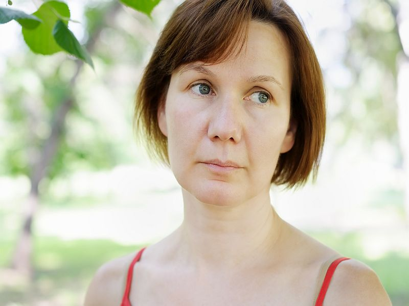 Pensive middle age woman, outdoors portrait