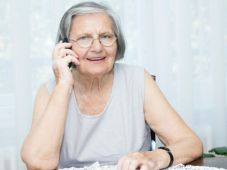 Senior woman sitting on the table and talking by phone.