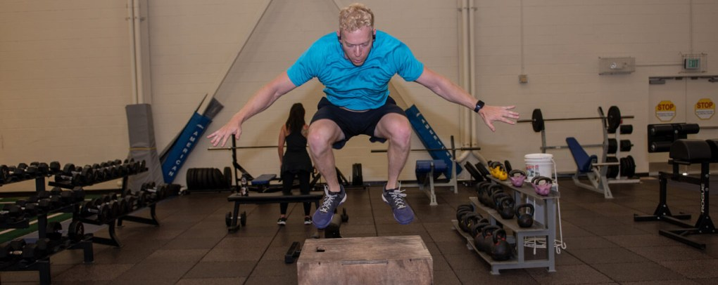 Man in blue shirt doing box jump in gym