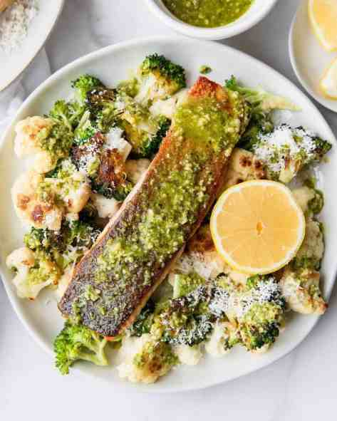 Crispy Pesto Salmon with oven roast parmesan cauliflower and broccoli. The perfect dinner, lunch, or healthy meal prep recipe by Healthful Blondie.