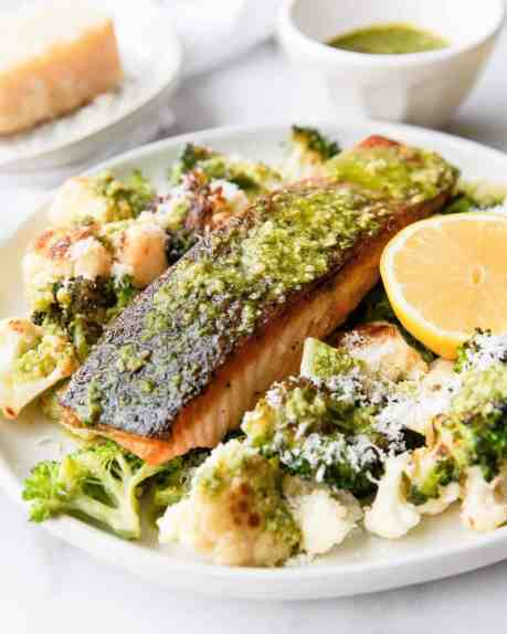 Pesto topped salmon with a side of delicious cheesy roasted vegetables. Ideal meal prep recipe for everyone! Perfect family dinner or date night dinner idea. Ready in 25 minutes! Recipe by Healthful Blondie.