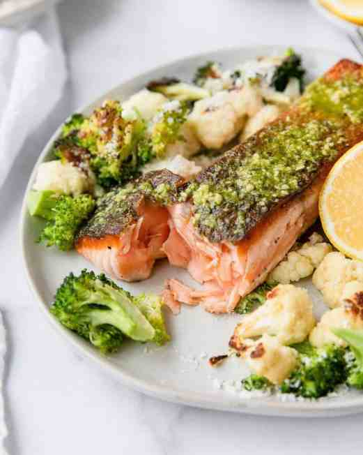 The ultimate flakey salmon with perfect crispy skin. This healthy dinner recipe is by Healthful Blondie x Tati Chermayeff. Topped with healthy pesto and lots of parmesan cheese for a gluten free dinner.