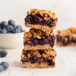 Healthy blueberry crumble bars topped with oatmeal crisp and stacked on top of each other. Easy vegan and gluten free blueberry pie bars.