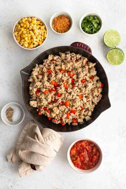 Ingredients in healthy taco stuffed sweet potatoes. This super healthy dinner has lean ground turkey, corn, salsa, lime, fresh tomato and onions, taco seasonings, and cilantro! The ideal healthy ingredient list for tacos.