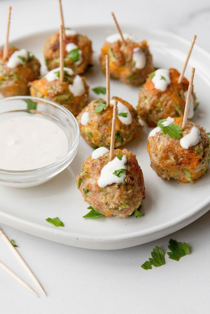 Healthy broccoli cheddar turkey meatball poppers with ranch dressing drizzled on top. Meatball appetizer sticks.