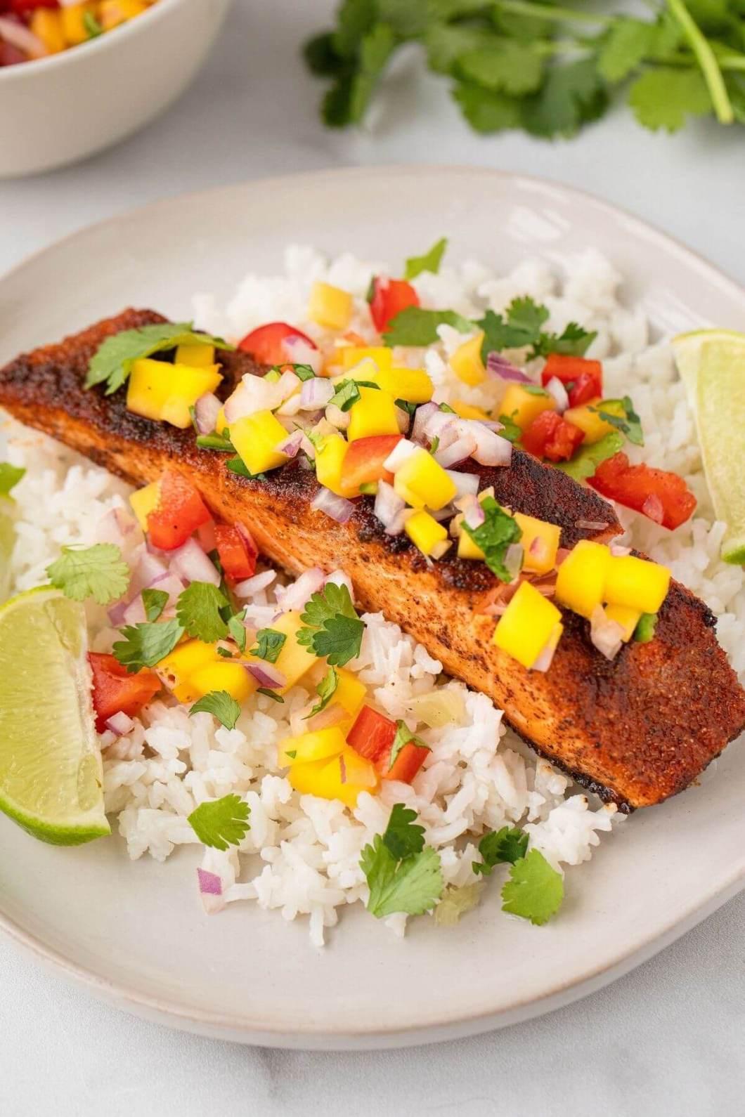 pan seared blackened salmon on rice with fresh mango salsa on top