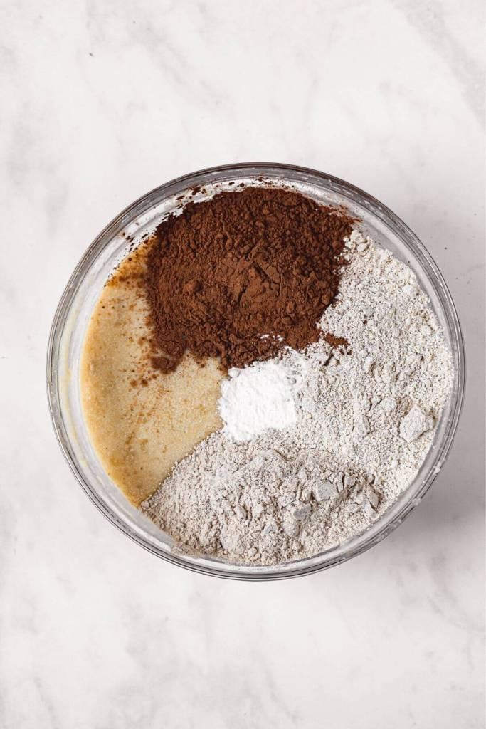 folding oat flour and whole wheat flour into banana bread batter