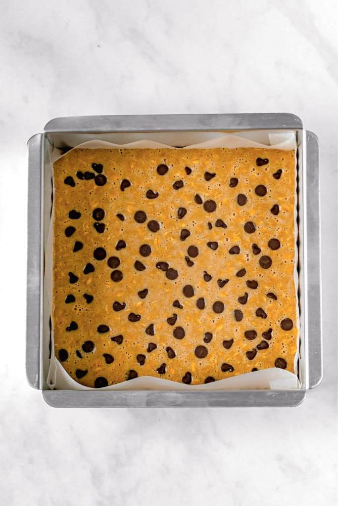 oatmeal bar batter in a a tin with chocolate chips on top