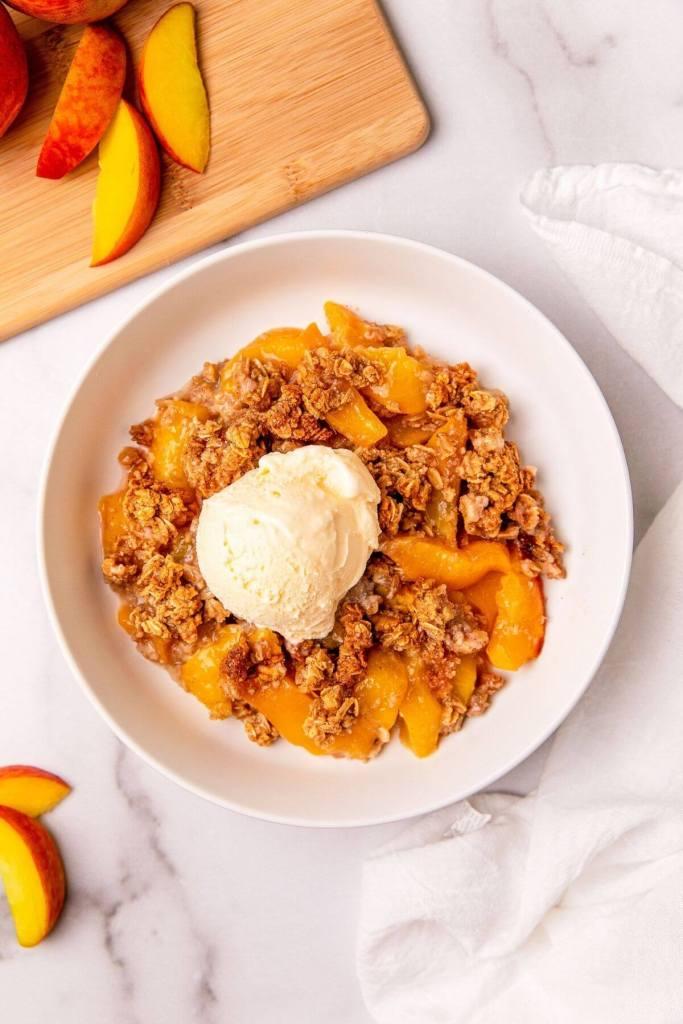 healthy peach crisp in a bowl with vanilla ice cream