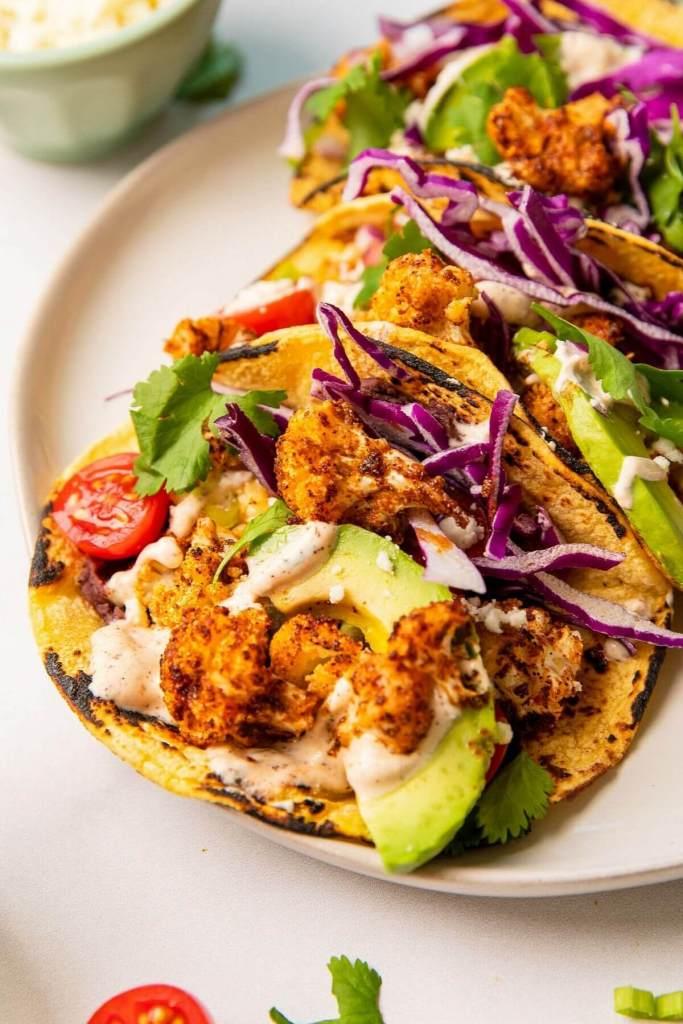 roasted cauliflower taco with crema, avocado, and black beans