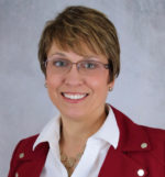 Amy Costello with short hair and glasses wearing a red jacket and white blouse